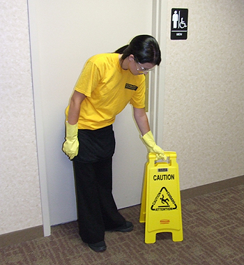 Space Management employee with caution wet floor sign