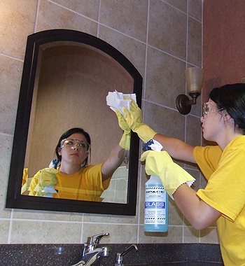 Space Management employee cleaning a restroom mirror