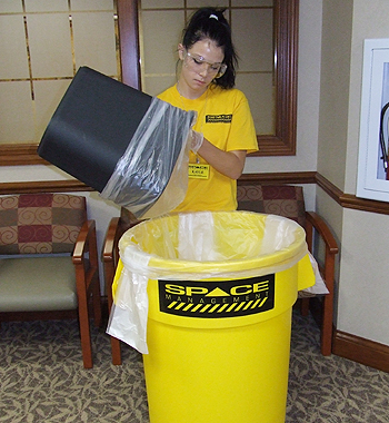 Space Management employee handling trash