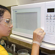 Space Management staff cleaning microwave